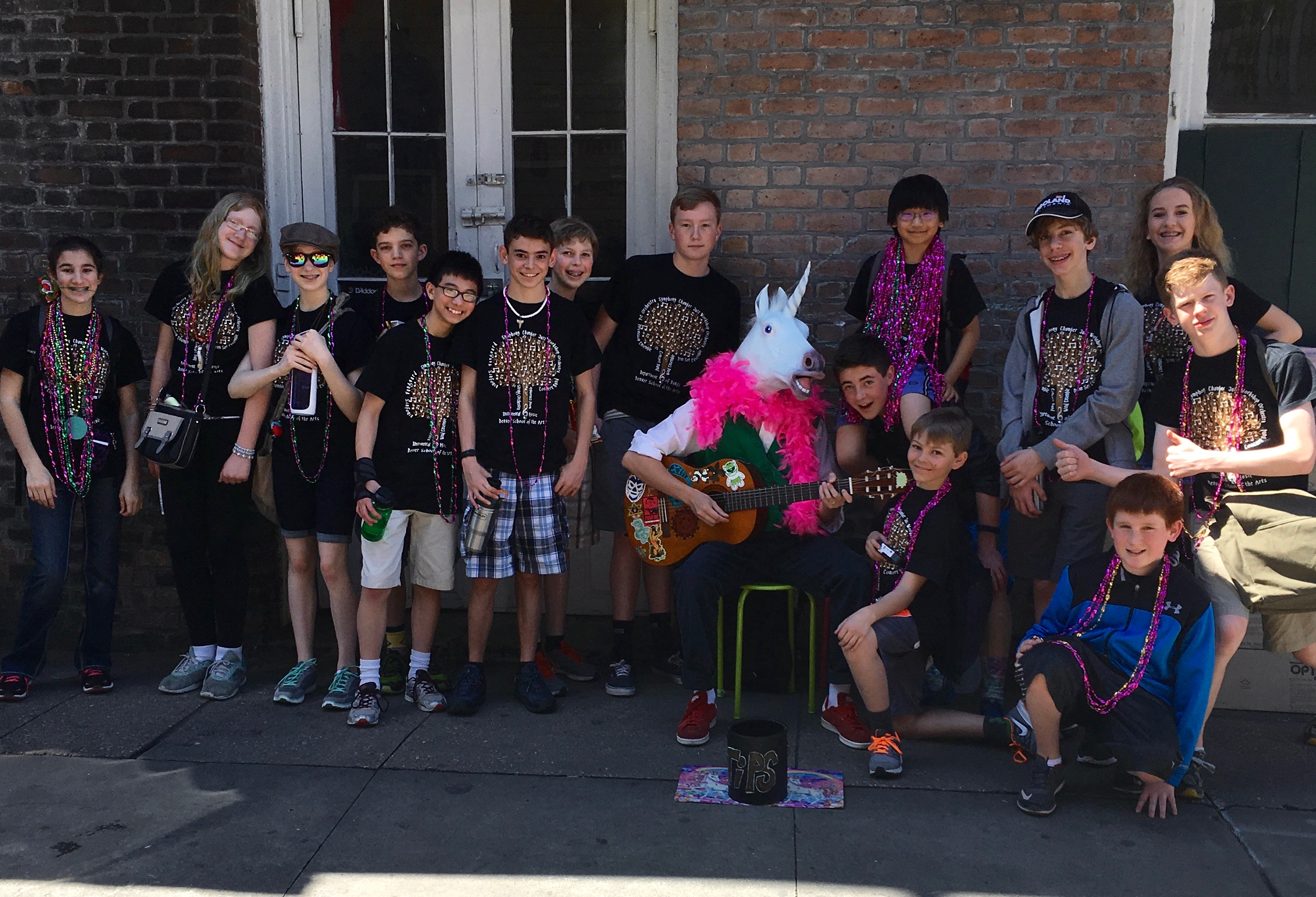 DSA students sit in with a guitar playing unicorn during French Quarter Fest.